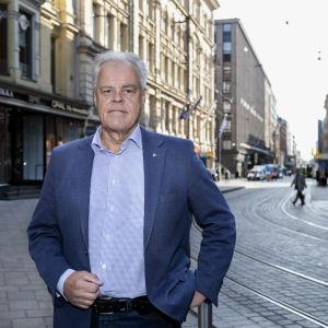 En gråhårig man i blå skjorta och kavaj står på en stenlagd gata i centrum av Helsingfors.
