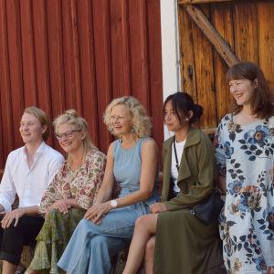 Fem personer som sitter bredvid varandra och skrattar.