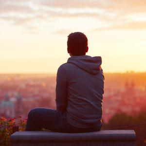 Man sitter och tittar ut över en stad i solnedgången.