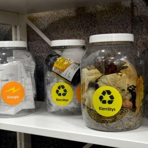 glasburkar med olika sorters skräp i som ska i olika återvinningskärl