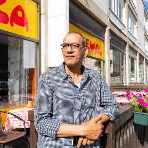 En man utanför sin restaurang.