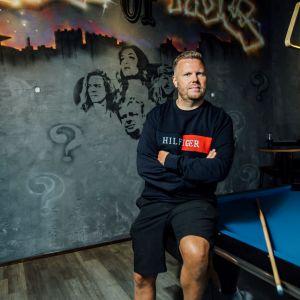 En man sitter på ett biljardbord, framför en schablonmålad vägg.