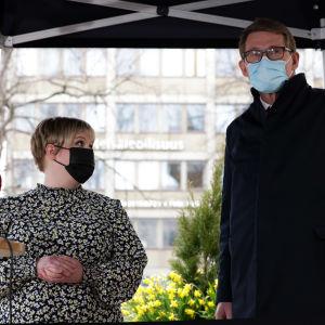 Annika Saarikko och Matti Vanhanen står under ett tält framför mikrofoner utomhus.