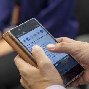 Någon håller i en smarttelefon. Man ser bara händerna och telefonen.