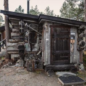 Liten stuga av torrfuru, verktyg, skinnfällar och djurhorn på väggarna.