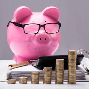 En spargris med glasögon står på ett bord. I förgrunden bland annat högar med slantar och en kalkylator.