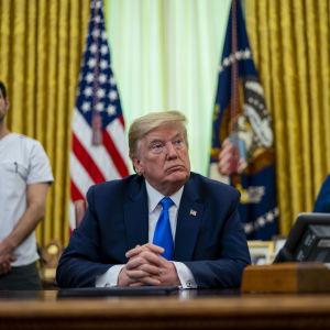 Yhdysvaltain presidentti Donald Trump työpöytänsä ääressä, taustalla sairaalatyöntekijöitä.