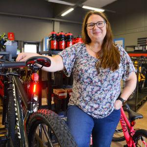 En kvinna i en cykelaffär, bredvid en cykel med baklykta.