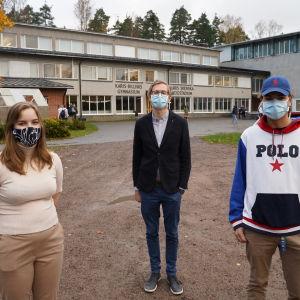 Tre personer med munskydd utanför Karis-Billnäs gymnasium.