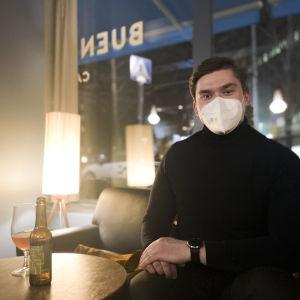 En man ser in i kameran, han har på sig munskydd. Han sitter inne i en bar, på bordet står en ölflaska och ett glas.