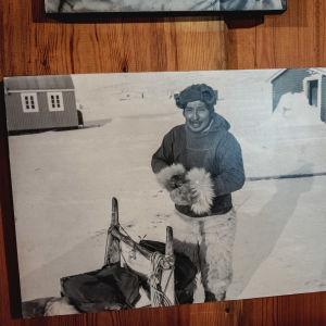 Mustavalkoinen kuva, turkiksiin pukeutunut mies katsoo kameraan