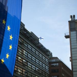 EU-flagga bredvid Kampens köpcenter i Helsingfors. Uppe i mitten syns en liten Finlands flagga och blå himmel.
