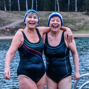Två glada kvinnor i mössa och baddräkt håller om varandra