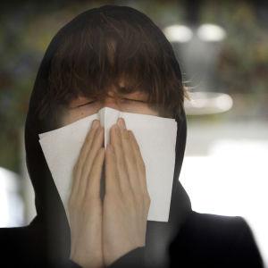 Nuori aivastaa kertakäyttöiseen nenäliinaan.