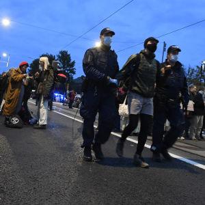 Poliisit siirtävät bussiin Syyskapina-mielenosoituksesta kiinniotettua ympäristöliike Elokapinan mielenosoittajaa eduskuntatalon edustalla Mannerheimintiellä.