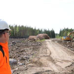En man med vit hjälm på huvudet ser på när en grävmaskin utgör markarbeten.