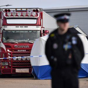 En uniformbeklädd polis framför en långtradare.