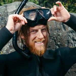 Juontaja Tom Nyludn maski ja snorkkeli päässä rannassa.