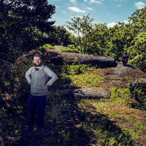 En man i luvtröja står på Muhkuriberget i Åbo, omgiven av träd.