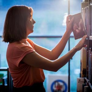 En kvinna i motljud tar ut en bok ur en hylla i biblioteket.