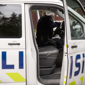 En polis i en polisbil.