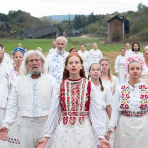 Vitklädda människor med öppna armar står i led och ser rakt fram, i bakgrunden syns ett sommarlandskap och en midsommarstång.