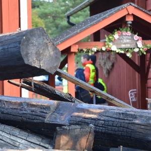 Brända stockar vid gammalt trähus.