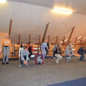 Barn i en stor sal som dansar och sjunger.