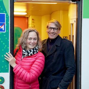 En glad man och en glad kvinna i en dörr till ett tåg.