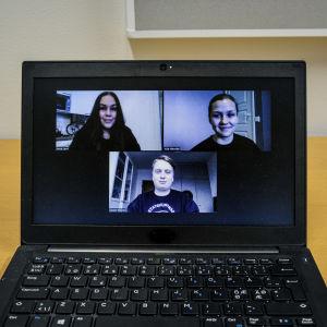 En laptopdator på ett bord. På skärmen syns tre unga personer i ett videosamtal.