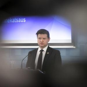 Mikko Koskinen står vid ett talarpodium.