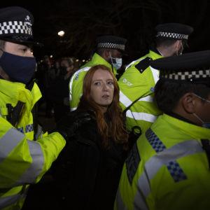 En kvinna omgiven av flera poliser. En av poliserna håller i kvinnans arm. Poliserna har munskydd.