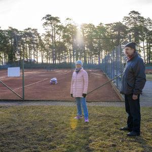 En kvinna och en man står bredvid tennisbanor. Det är ute, tidig vår och gäller utomhusbanor.