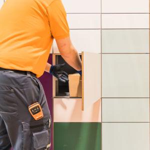 Kuorma-auton kuljettaja Joona Lyytikäinen jakaa paketteja pakettiautomaattiin.