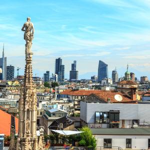 Vy över Milano med en kyrka i förgrunden och staden med skyskrapor i bakgrunden.