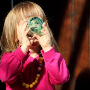 Flicka dricker ur ett vattenglas.