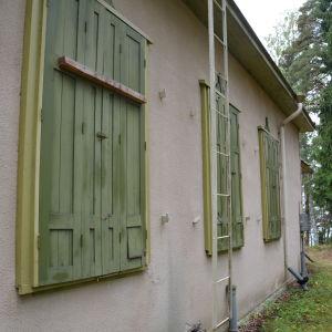 De gröna fönsterluckorna på baksidan av Villa Ståhlström hålls stängda under vintern.