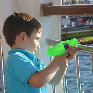 Pojke leker med vattenbössa på färja