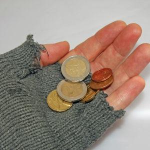 Hand med vante utan fingerskydd. Några euroslantar i handen.