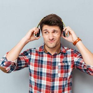 En man som lyssnar på något i hörlurar. Han ser missnöjd ut och det ser ut som om han håller på att ta av sig lurarna.