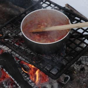 Kuva kattilasta, jossa valmistuu chorizomakaronimössöä nuotiolla.