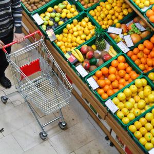 En person skuffar en kundvagn framför ett stort sortiment av bland annat citrusfrukter.