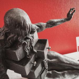 En av Salvador Dalís konstverk. En staty på en liggande person med långt hår hängande över ögonen som har byrålådor som kommer ut ur kroppen.