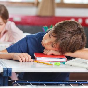 en pojke ligger på en skolbok