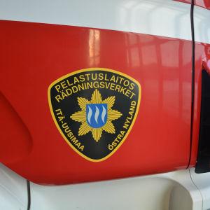 Östra Nylands räddningsverk logo på brandbilsdörr