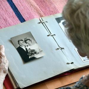 Gammal kvinna ser på ett gammalt bröllopsfoto i ett fotoalbum