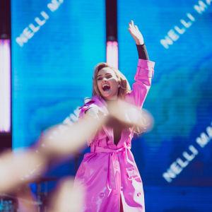 Nelli Matula esiintymässä vaaleanpunaisessa trenssissä YleXPopissa 2018.