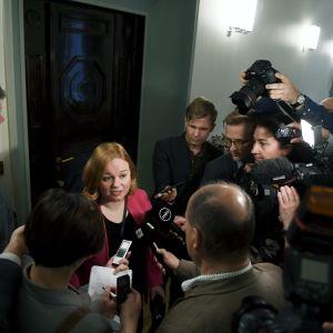 Krista Kiuru (SDP) omringad av journalister utanför utskottsdörren.