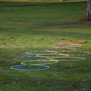 Tio rockringar som ligger på en gräsmatta, formade som ett kors (ungefär). Ska föreställa rutor i hoppa hage.