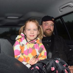 ett barn, flicka och en vuxen man (pappan) sitter i baksätet i en personbil.